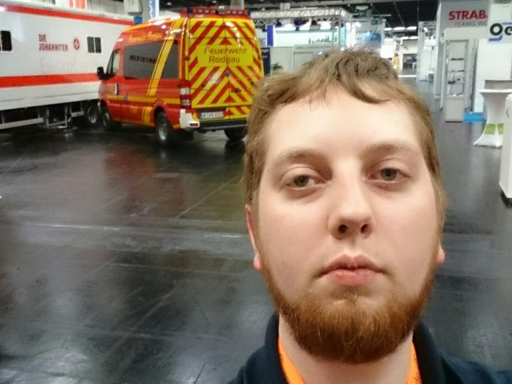 Mir wurde gesagt, ich sollte mehr Selfies von mir machen - da hab ich eins mit ein paar der Fahrzeuge aus der Halle im Hintergrund gemacht.